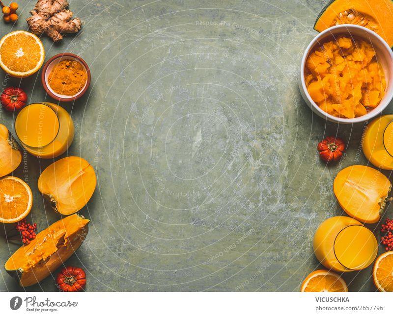 Orangefarbene Smoothie-Zutaten als Hintergrund für die kalte Jahreszeit mit Kürbis, Orangenfrüchten, Ingwer, Kurkuma und Kaki, Draufsicht, Rahmen, Kopierraum. Smoothie-Getränke für gesunde Stimmung und Energie
