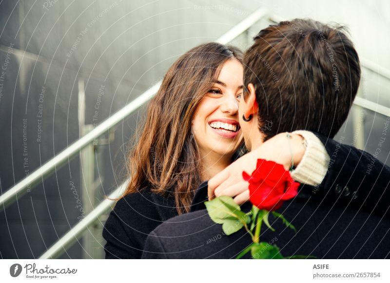 Ein glückliches Paar, das in eine Rose auf der Straße verliebt ist. Freude Glück schön Winter Feste & Feiern Valentinstag Frau Erwachsene Mann Hand Herbst Blume