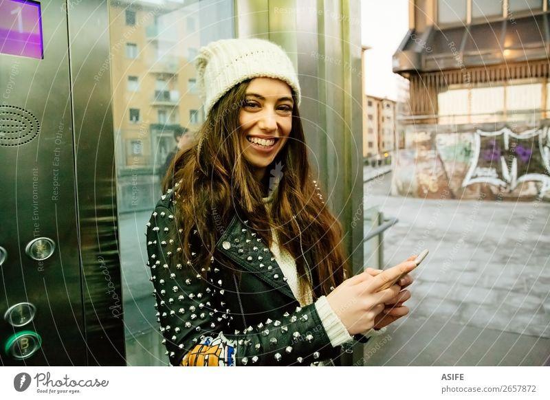 Junge Frau in der Stadt, die Telefon im Aufzug benutzt. Lifestyle Freude Glück schön lesen Winter PDA Technik & Technologie Internet Erwachsene Jugendliche Hand