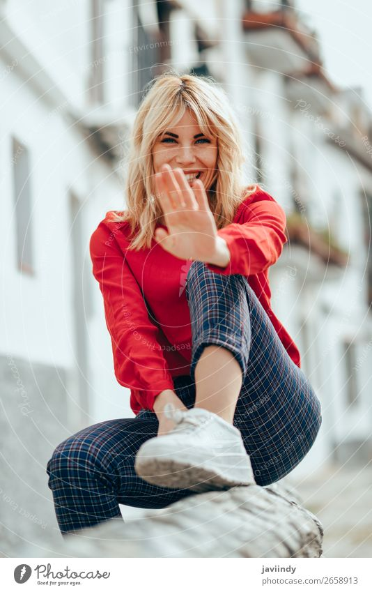 Eine Frau, die im Freien sitzt und ihre Hand in die Nähe der Kamera legt. Lifestyle schön Haare & Frisuren Mensch feminin Junge Frau Jugendliche Erwachsene 1