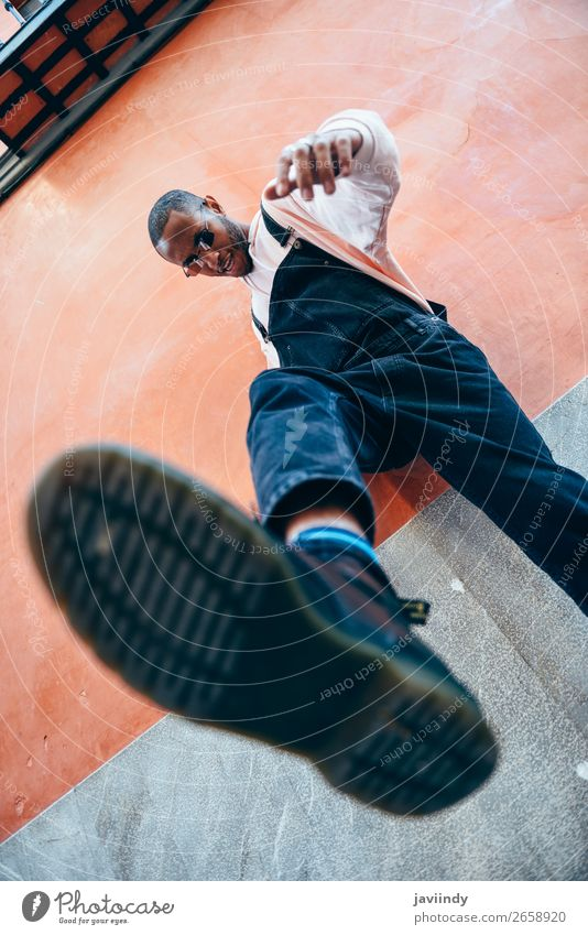 Junger schwarzer Mann, der auf den Boden tritt. Lifestyle schön Mensch maskulin Junger Mann Jugendliche Erwachsene 1 18-30 Jahre Straße Hemd Sonnenbrille stehen
