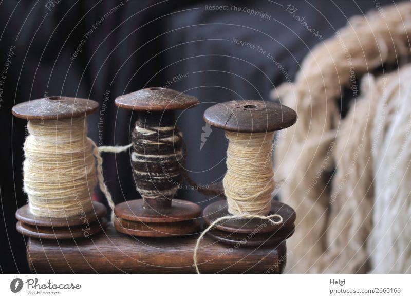 drei historische Garnspindeln aus Holz mit verschiedenen Garnen Wolle Schnur Spule Garnspulen liegen stehen alt außergewöhnlich einzigartig retro blau braun