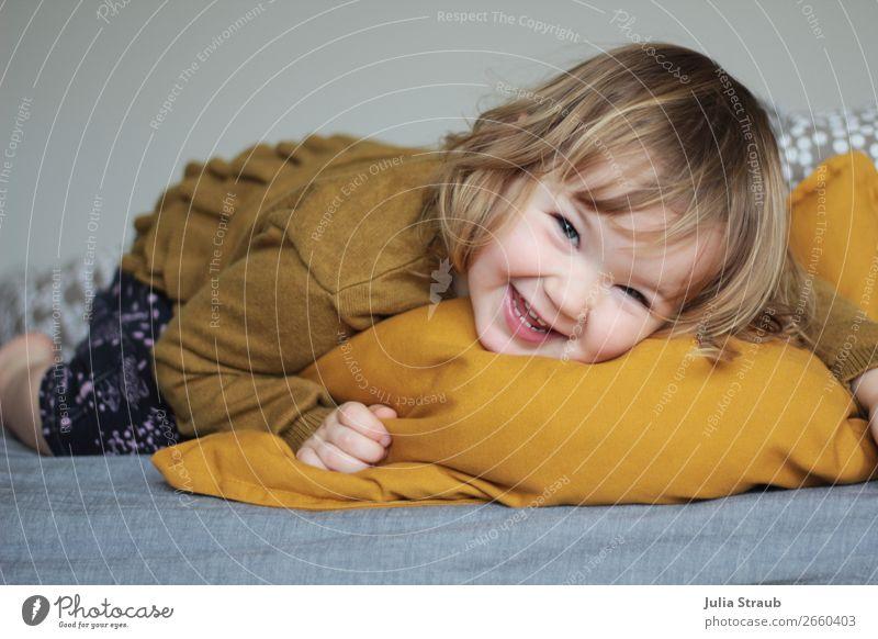 Kleinkind liegt auf einem Kissen und lacht Bett Schlafzimmer feminin Mädchen Kindheit 1 Mensch 1-3 Jahre Hose Pullover brünett blond Locken Pony Bewegung lachen
