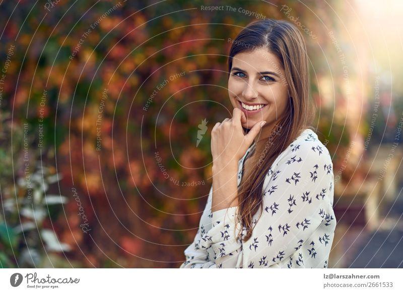 Attraktive junge Frau in einer bunten Herbststraße Glück Erwachsene 1 Mensch 18-30 Jahre Jugendliche Blatt Straße Mode brünett Lächeln lachen Fröhlichkeit klug