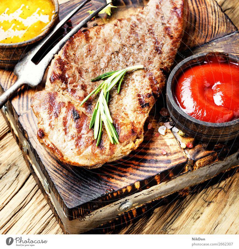 Rindersteak mit Rosmarinzweig Rindfleisch Steak Fleisch Lebensmittel gegrillt Barbecue gebraten Beefsteak Grillrost Saucen Ketchup Lendenstück hölzern Filet