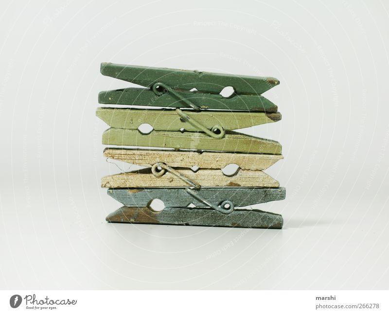 Klammern in einer 4er-Beziehung blau weiß grün Holz braun Zeichen Stapel