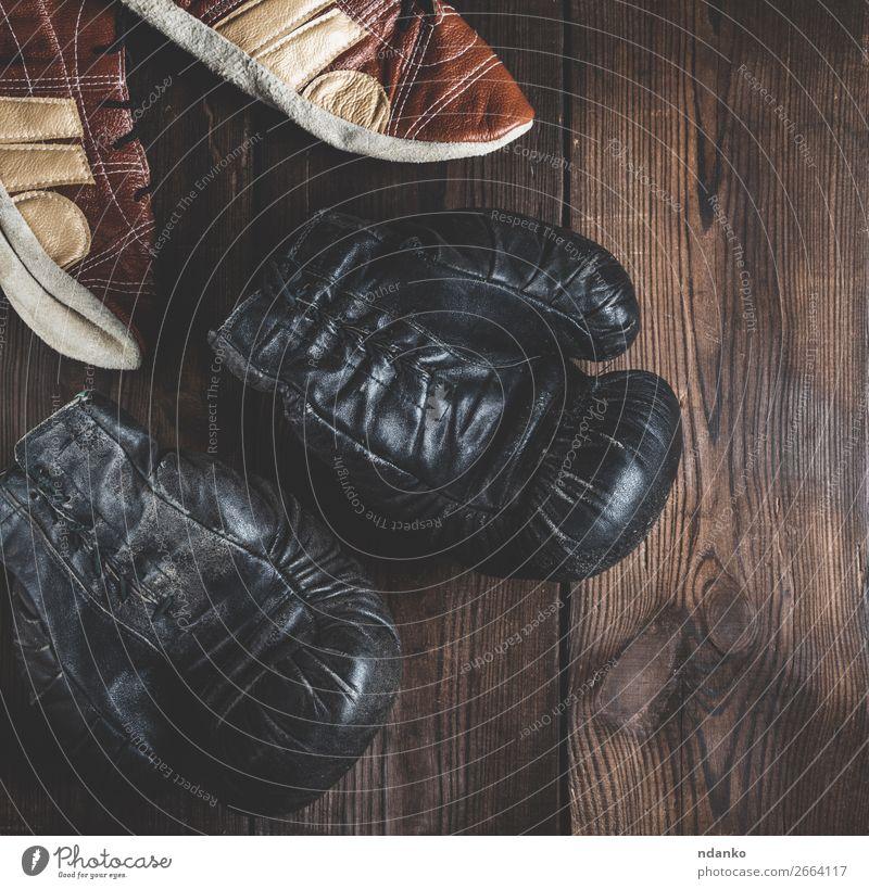 Paar sehr alte schwarze Boxhandschuhe aus Leder Lifestyle Fitness Sport Erfolg Handschuhe Schuhe Holz dunkel retro braun Schutz Konkurrenz Nutzholz rustikal