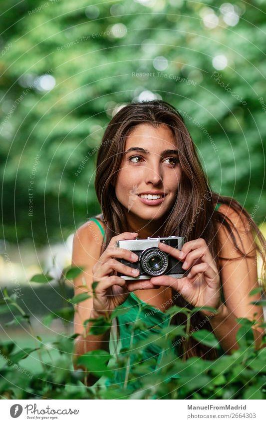junge schöne Touristenfrau mit einer Fotokamera Lifestyle Glück Ferien & Urlaub & Reisen Tourismus Sommer Mensch Frau Erwachsene Baum Park Straße Mode Hut