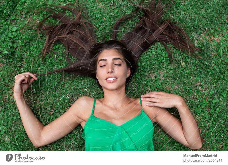 junge, fröhliche Frau, die sich auf das Gras legt. Lifestyle Glück schön Freizeit & Hobby Sommer Mensch Erwachsene Natur Park Wiese Lächeln authentisch