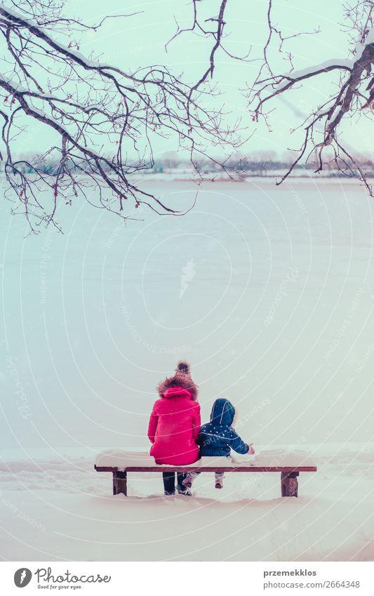 Mutter und ihre Tochter sitzen an winterlichen Tagen auf einer Bank. Lifestyle Freude Glück Winter Schnee Winterurlaub Mensch Kind Kleinkind Mädchen Junge Frau