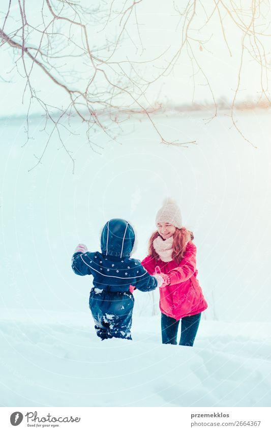 Teenagermädchen genießt Schnee mit ihrer kleinen Schwester Lifestyle Freude Glück Winter Winterurlaub Mensch Kind Kleinkind Mädchen Frau Erwachsene Mutter