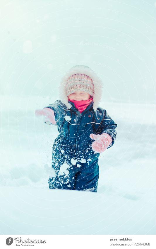 Fröhliches kleines Mädchen genießt den Schnee. Kind, das draußen spielt und im Winter bei Schneefall durch tiefen Schnee läuft. Kleinkind trägt dunkelblauen Schneeanzug