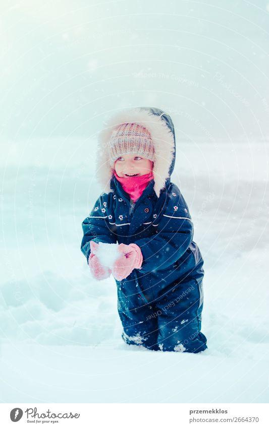 Glückliches kleines Mädchen genießt Schnee im Winter bei Schneefall. Lifestyle Freude Winterurlaub Kind Kindheit 1 Mensch 3-8 Jahre genießen Zusammensein weiß