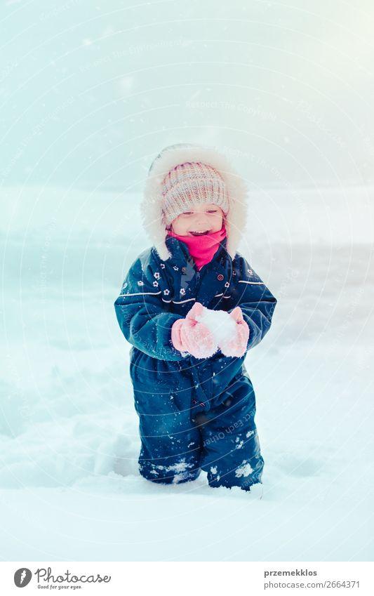Glückliches kleines Mädchen genießt Schnee im Winter bei Schneefall. Lifestyle Freude Winterurlaub Kind Kleinkind Kindheit 1 Mensch 3-8 Jahre Eis Frost Mütze