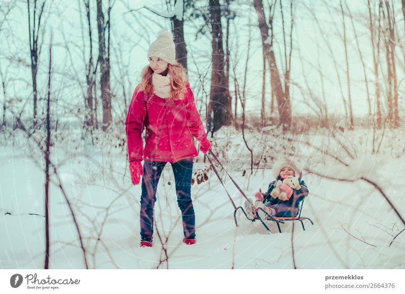 Teenagermädchen zieht mit ihrer kleinen Schwester Schlitten durch den Wald. Lifestyle Freude Glück Winter Schnee Winterurlaub Mensch Kind Baby Kleinkind Mädchen