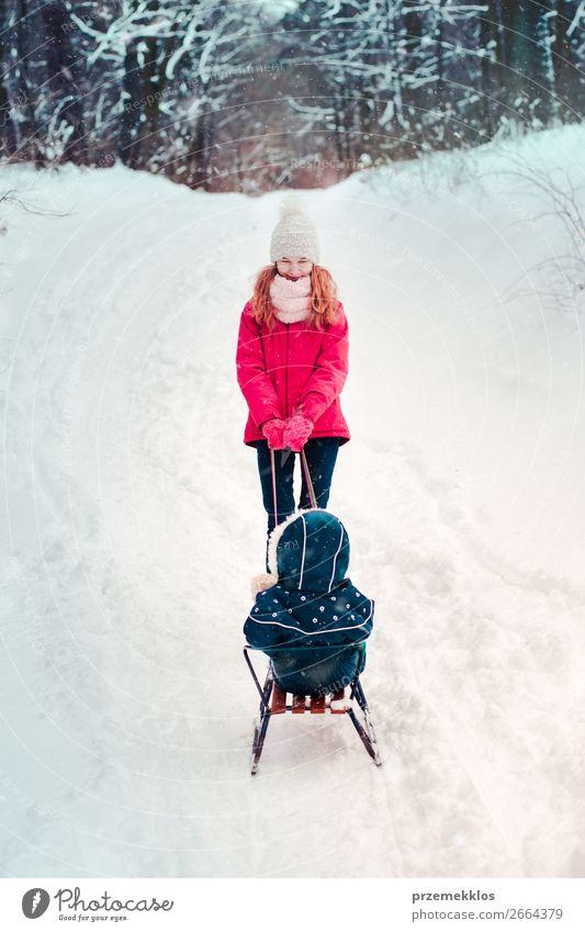 Teenagermädchen zieht mit ihrer kleinen Schwester Schlitten durch den Wald. Lifestyle Freude Glück Winter Schnee Winterurlaub Mensch Kind Mädchen Junge Frau