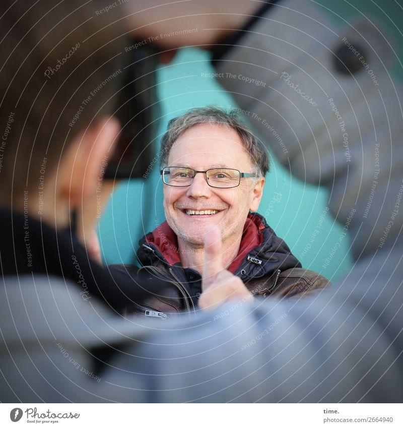 Daumenkino Fotokamera maskulin Mann Erwachsene 2 Mensch Mauer Wand Jacke Brille brünett kurzhaarig Lächeln lachen Freude Zufriedenheit Lebensfreude Begeisterung