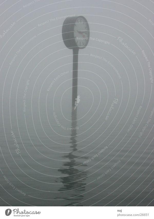 Nebeluhr Wasser grau See Nebel Uhr obskur Hochwasser Ausstellung Wasseroberfläche Weltausstellung Bahnhofsuhr