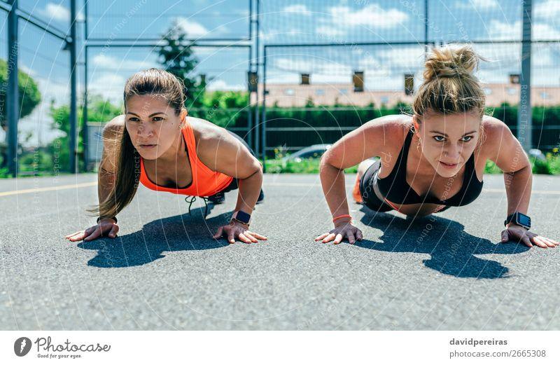 Sportlerinnen bei Liegestützen Lifestyle schön Körperpflege Mensch Frau Erwachsene Freundschaft brünett blond Fitness sportlich stark Kraft anstrengen Energie