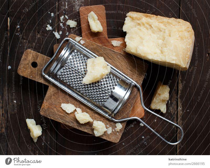 Gereifter Parmesankäse Käse Holz alt dunkel braun gelb parmiggiano geschreddert Textfreiraum Molkerei Lebensmittel Feinschmecker Hartkäse Zutaten Italienisch