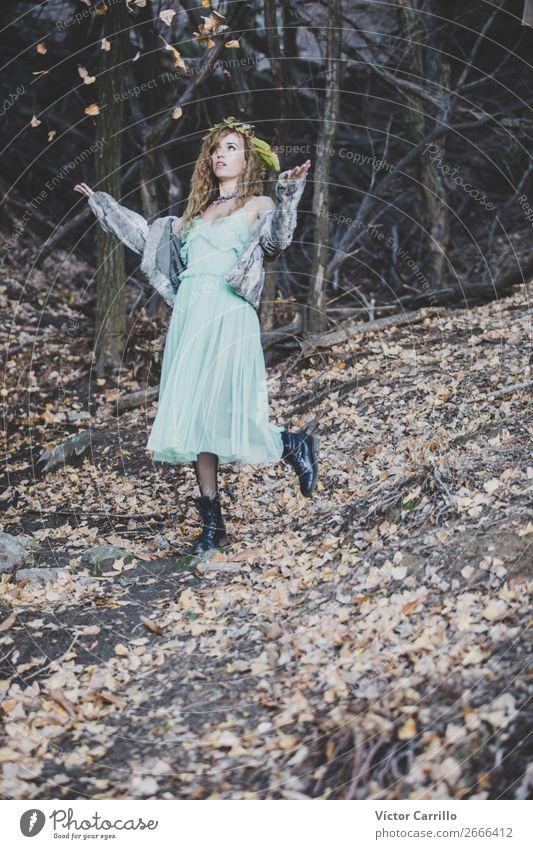 Eine junge Frau spielt mit Blättern im Wald. Lifestyle elegant Stil Design exotisch Freude schön Leben harmonisch Wohlgefühl Mensch feminin Junge Frau