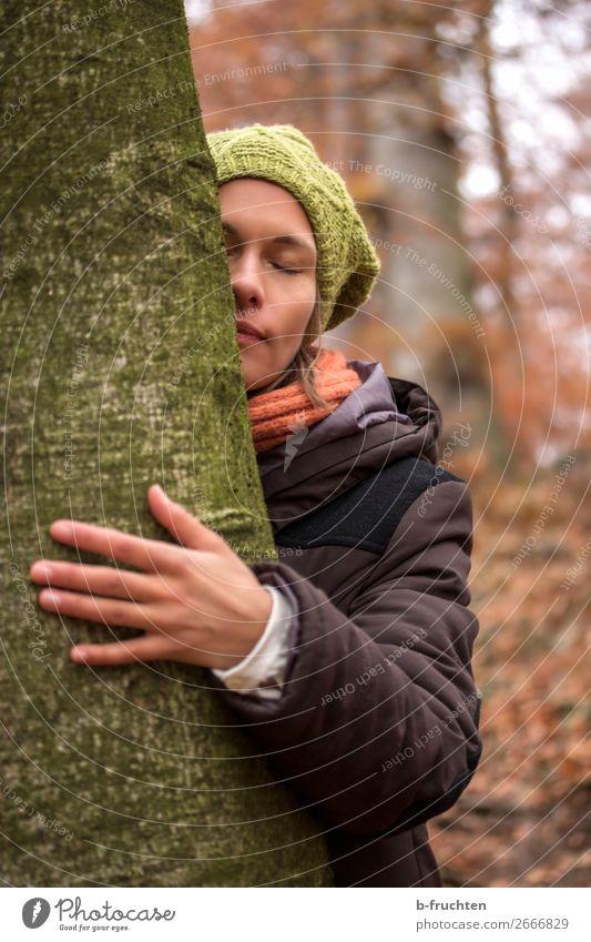 Frau mit Wollmütze, Schal und Wintermantel umarmt Baum Sinnesorgane Erholung ruhig Meditation Erwachsene Gesicht Hand Herbst Park Wald berühren stehen träumen