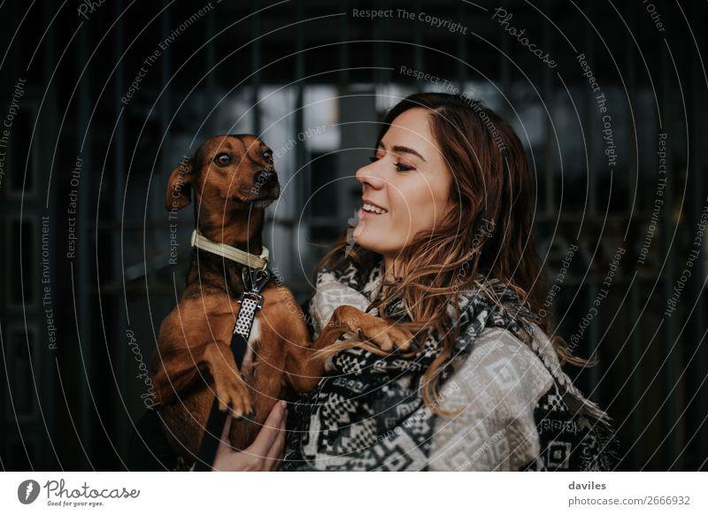 Weißes lächelndes Mädchen, das ihren Hund in den Armen hält. Lifestyle Freude Junge Frau Jugendliche Erwachsene Freundschaft 1 Mensch 30-45 Jahre Stadt Schal