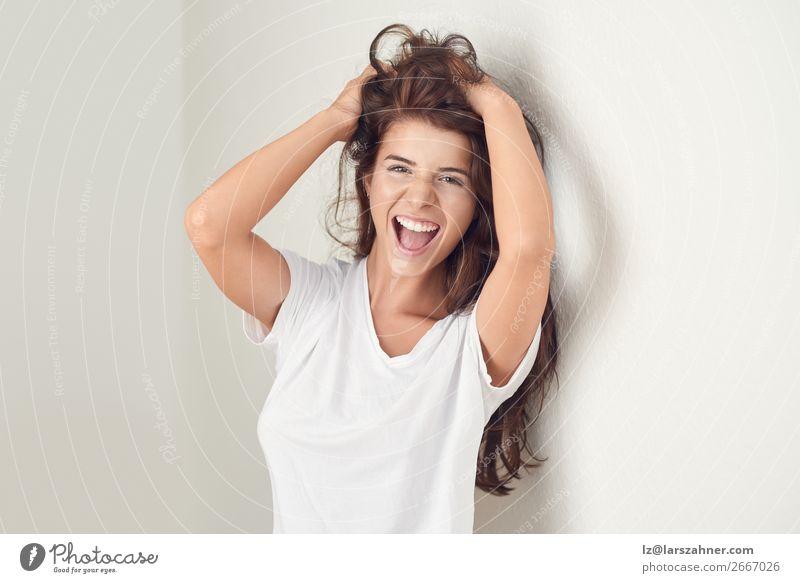 Junge lächelnde brünette Frau, die sich an die Wand lehnt. Lifestyle Glück schön Körper Haut Gesicht Schminke Behandlung Erwachsene 1 Mensch 18-30 Jahre