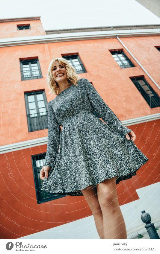 Lustige junge blonde Frau, die auf einem urbanen Hintergrund steht. Lifestyle Stil Freude Glück schön Haare & Frisuren Mensch feminin Erwachsene Jugendliche 1