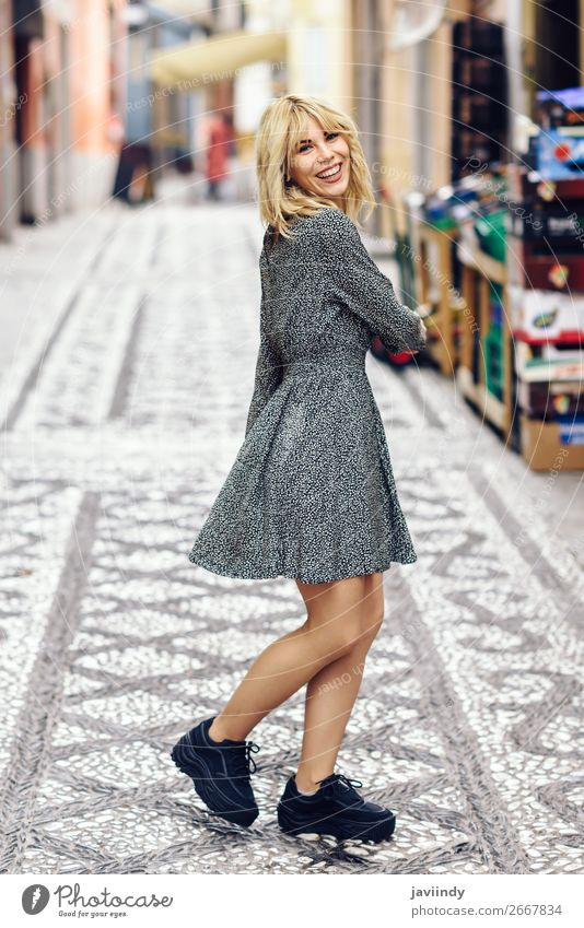 Lustige junge blonde Frau, die auf einem urbanen Hintergrund steht. Lifestyle Stil Freude Glück schön Haare & Frisuren Mensch feminin Junge Frau Jugendliche