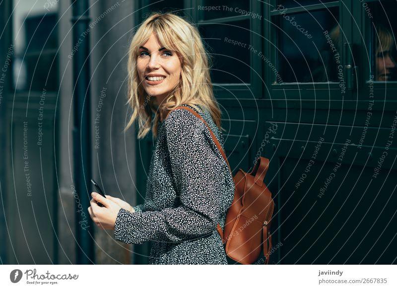 Junge kaukasische Frau schaut auf ihr Smartphone im Freien. Lifestyle Stil schön Haare & Frisuren Telefon PDA Mensch feminin Junge Frau Jugendliche Erwachsene 1