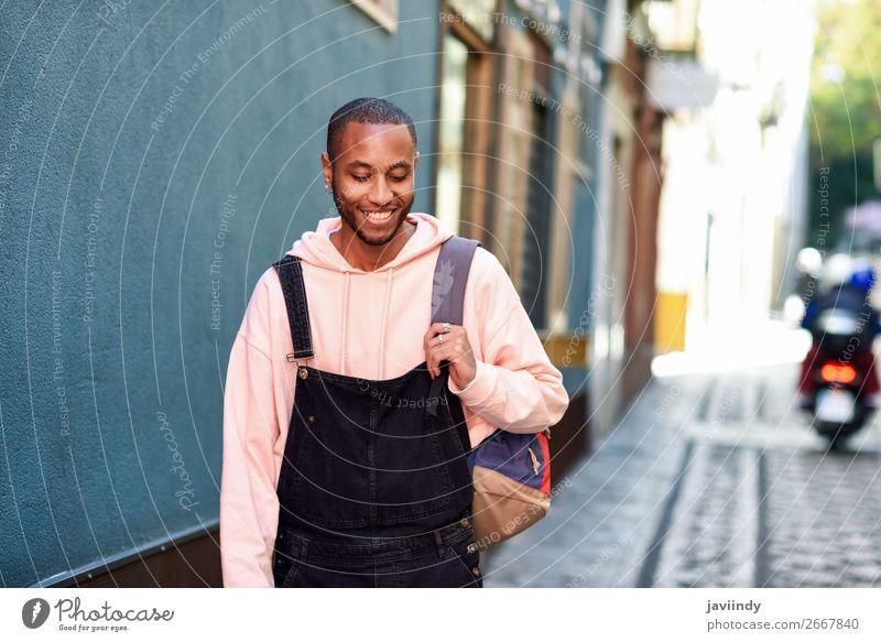 Junger schwarzer Mann, der lächelnd die Straße hinuntergeht. Lifestyle Glück schön Mensch maskulin Junger Mann Jugendliche Erwachsene 1 18-30 Jahre Mode