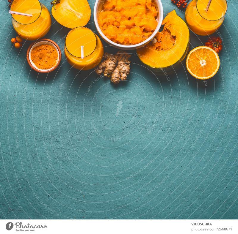 Gesunder Kürbis-Smoothie in Gläsern mit orangefarbenen Zutaten: Kaki, orangefarbene Früchte, Ingwer- und Kurkumapulver auf blauem Hintergrund, Ansicht von oben. Immunitätsförderndes Entgiftungsgetränk für die kalte Jahreszeit