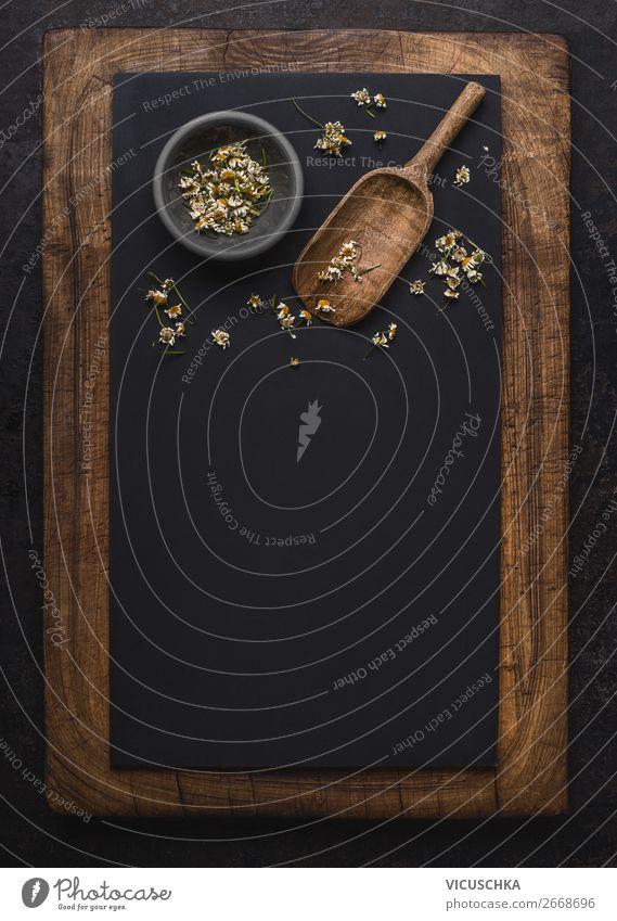 Dunkler Kreidehintergrund mit getrockneten Kamillenblüten und Holzschaufellöffel , Draufsicht mit Kopierraum für Ihren Entwurf. Heilkräuter und Kräutermedizin-Konzept. Senkrecht