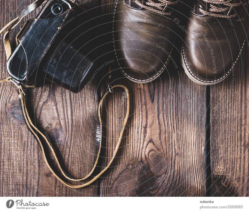 lederne braune Schuhe und eine alte Vintage-Kamera. Stil Design Fotokamera Fuß Mode Bekleidung Leder Holz Top Aussicht klassisch Hintergrund altehrwürdig lässig