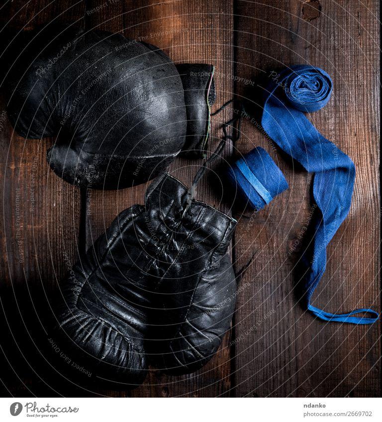 Paar sehr alte schwarze Boxhandschuhe aus Leder Lifestyle Fitness Sport Seil Ring Handschuhe Holz retro blau braun Schutz Konkurrenz Macht Kraft Stil Aktion