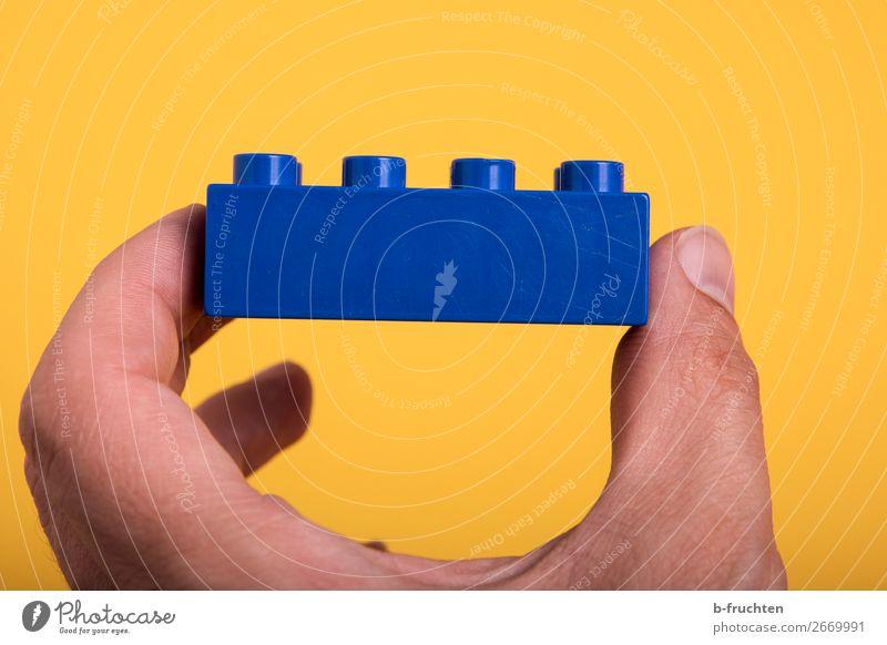 Spiel-Baustein in der Hand Finger Spielzeug Kunststoff wählen bauen berühren festhalten blau Optimismus Erfolg Idee Teamwork zusammenbauen Teile u. Stücke