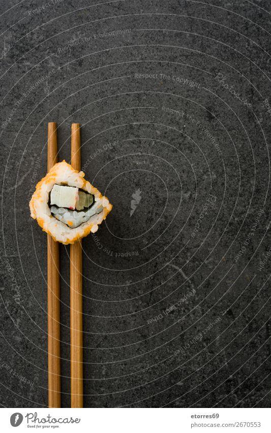 Essstäbchen mit Sushi auf schwarzem Stein. Lebensmittel Gesunde Ernährung Foodfotografie Japanisch Reis Fisch Lachs Meeresfrüchte Brötchen Mahlzeit machen
