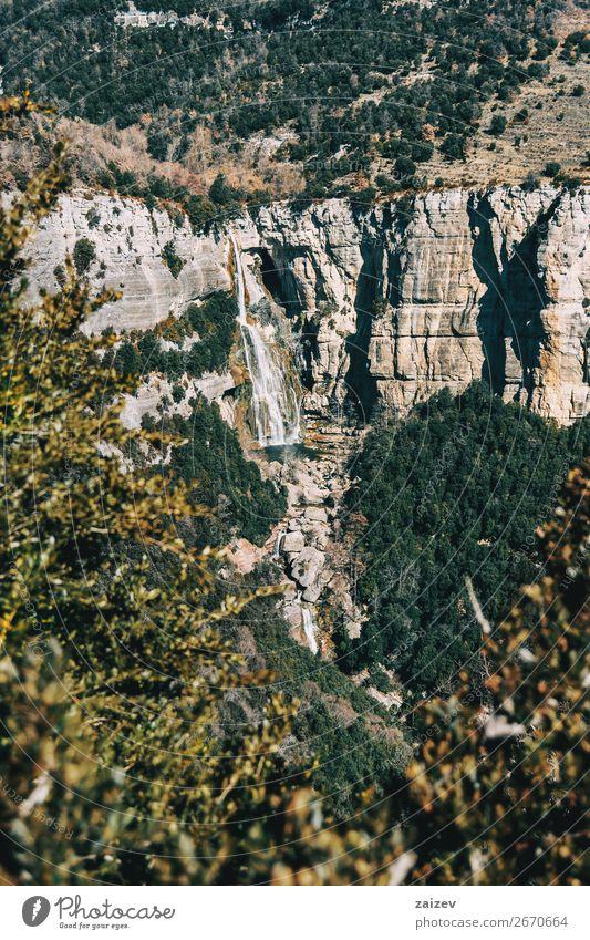 Detail einer Klippe mit einem Wasserfall, eingerahmt von den Blättern einiger Bäume schön Windstille Ferien & Urlaub & Reisen Abenteuer Berge u. Gebirge wandern