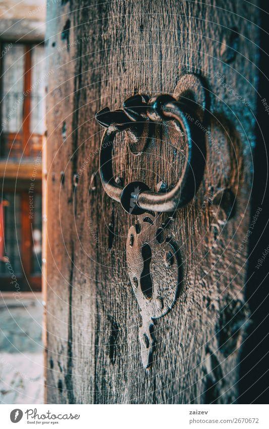 Ein Schloss und eine Klinke einer mittelalterlichen Holztür, aufgenommen von der Seite mit der Straße des Dorfes im Hintergrund Design Ferien & Urlaub & Reisen