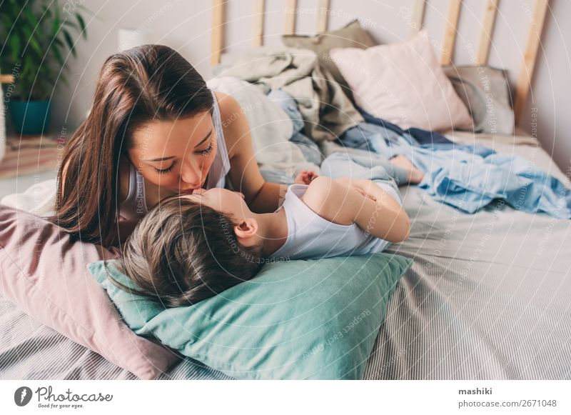 Mutter küsst ihren Kleinkind-Sohn im Bett für eine gute Nacht. Lifestyle Freude Glück Leben Erholung Spielen Schlafzimmer Kind Junge Eltern Erwachsene