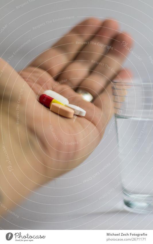 Männer, die Pillen in verschiedenen Farben neben einem Glas Wasser zeigen. Schalen & Schüsseln Behandlung Krankheit Medikament Wissenschaften Hand Holz blau