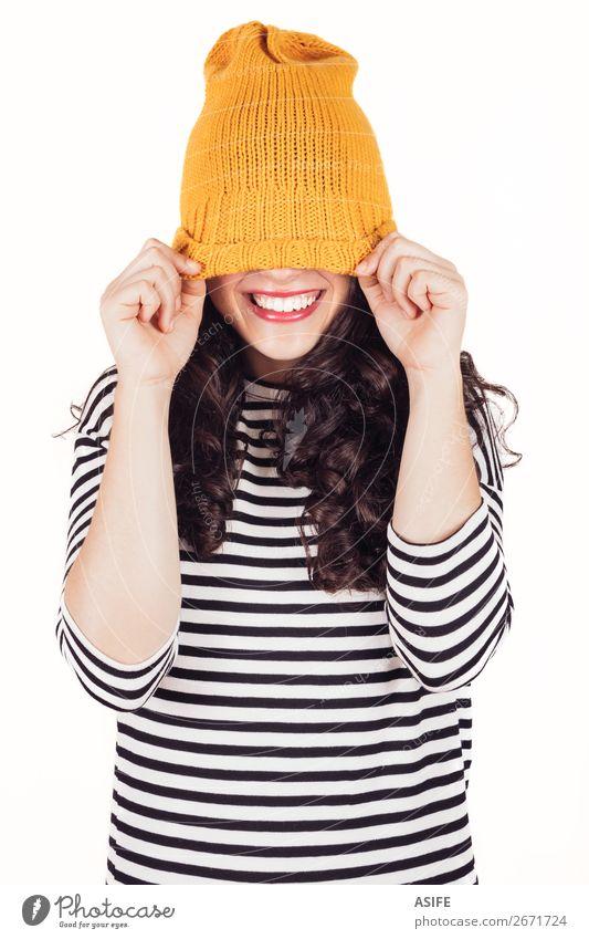 Fröhliches Herbst- oder Wintermädchen, das das Gesicht mit Wollmütze bedeckt. Glück schön Frau Erwachsene Zähne Kleid Lächeln Fröhlichkeit lustig gelb schwarz