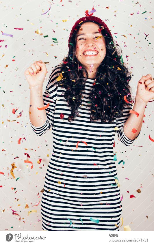 Lachendes Mädchen mit gestreiftem Kleid und Wollmütze unter einem Konfettiregen Freude Glück schön Feste & Feiern Geburtstag Frau Erwachsene brünett Lächeln