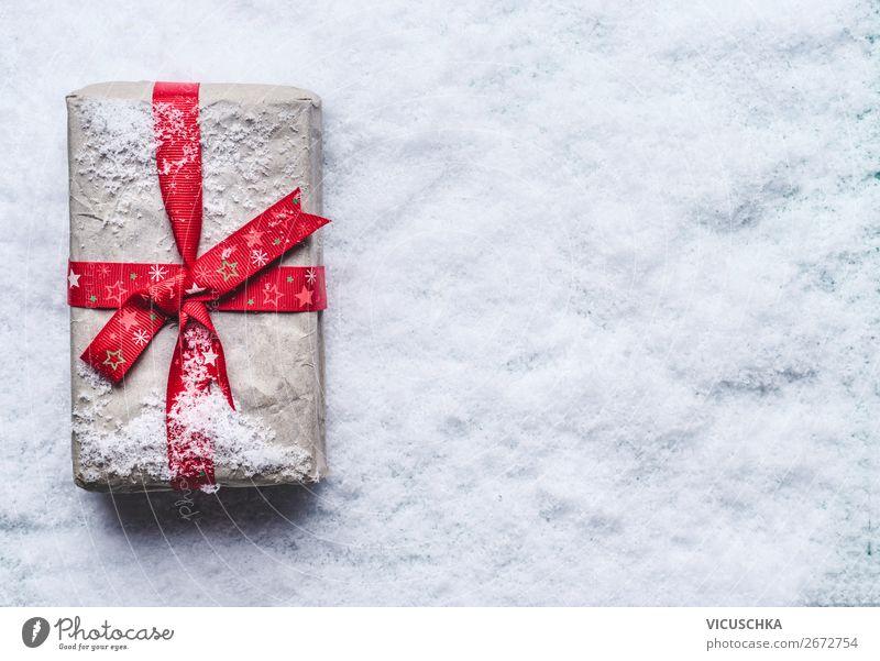 Weihnachtsgeschenk mit roter Schleife in Schnee Weihnachten & Advent Winter Hintergrundbild Feste & Feiern Stil Design Dekoration & Verzierung kaufen Zeichen