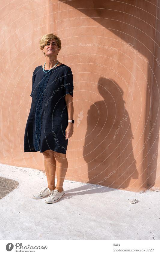 Standpunkt Frau Mensch Ferien & Urlaub & Reisen Sonne Haus Erwachsene Leben Wand Wege & Pfade feminin Mauer Fassade Kraft Lächeln 45-60 Jahre stehen