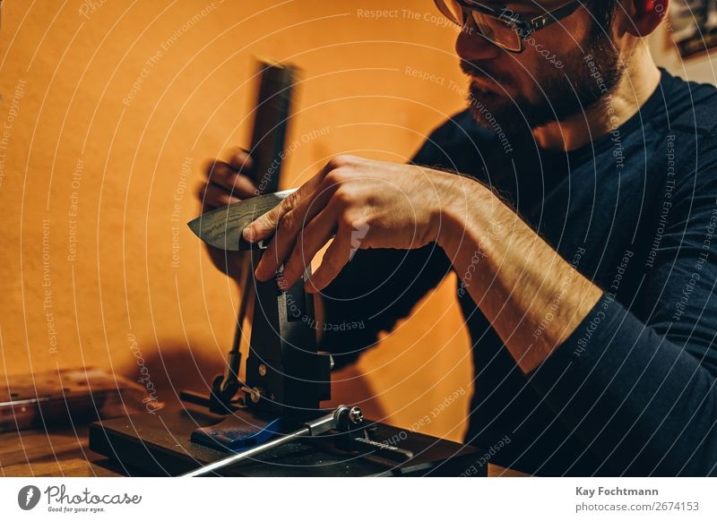 Mann schärft Messer Schleifmittel Vollbart Klinge Nahaufnahme Konzentration Essen zubereiten Handwerk Kunsthandwerker geschnitten Kompetenz Grinden
