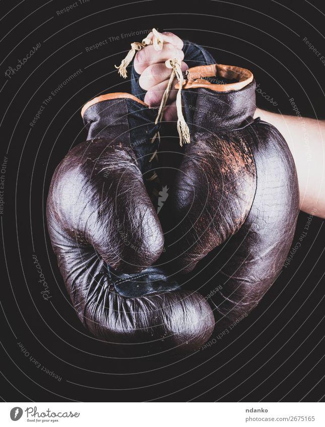 Paar Ledersportboxhandschuhe in der Hand Sport Erfolg Handschuhe alt Fitness braun schwarz Kraft Schutz Konkurrenz Kasten Boxer Boxsport Gerät üben kämpfen