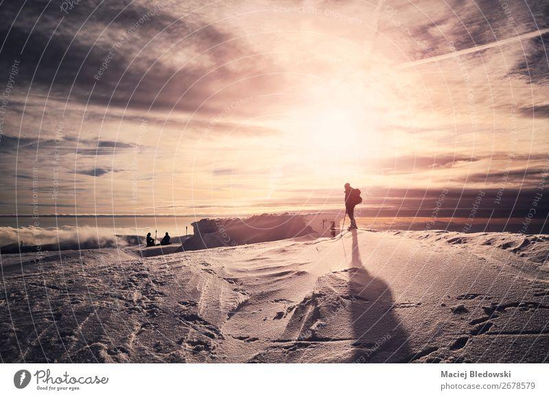 Winterberge mit ruhigen Skifahrersilhouetten bei Sonnenuntergang. Lifestyle schön Erholung Ferien & Urlaub & Reisen Ausflug Abenteuer Freiheit Expedition Schnee