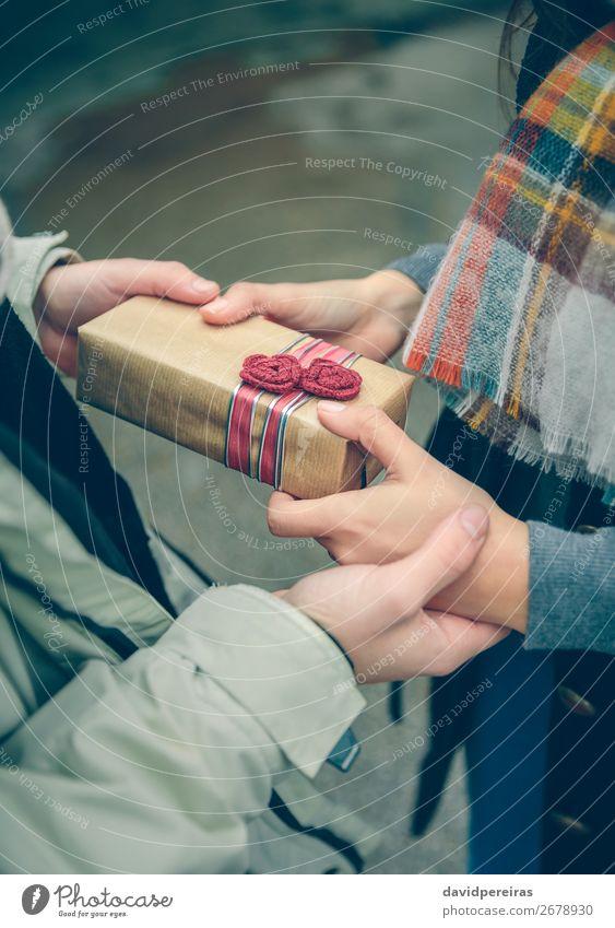 Männerhände geben Geschenkbox an Frau mit Schal Lifestyle Glück Winter Feste & Feiern Geburtstag Mensch Erwachsene Mann Paar Hand Herbst Blume Straße Schnur